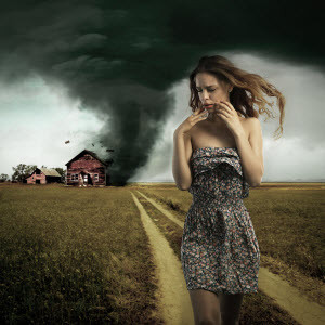 Woman walking away from a tornado hitting a house.