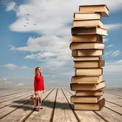 Woman beside a tower of books.