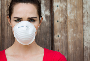 Woman wearing a mask avoiding the toxic mold in her house.