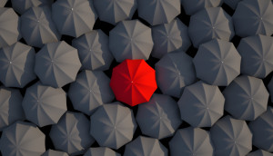 Top view of a red umbrella at the center among the other black umbrellas.